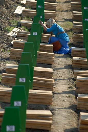 A Bosnian Muslim woman weeps near the grave of her relative among the graves of Srebrenica victims at the Memorial Cemetery in Potocari, near Srebrenica, 160 kms northeast of Sarajevo, Bosnia, Wednesday, July 11, 2012. (AP Photo/Sulejman Omerbasic)