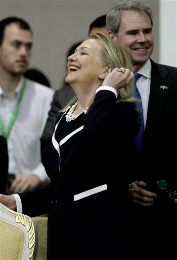U.S. Secretary of State Hillary Rodham Clinton, center, laughs before taking her seat during the 2nd East Asia Summit (EAS) Foreign Ministers' Meeting in Phnom Penh, Cambodia, Thursday, July 12, 2012. (AP Photo/Heng Sinith)