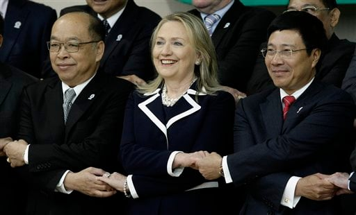 U.S. Secretary of State Hillary Rodham Clinton, center, shakes hands with her counterparts Pham Binh Minh, right, of Vietnam, and Surapong Tovichakchaikul, left, of Thailand on Thursday, July 12, 2012. (AP Photo/Heng Sinith)