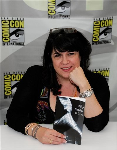 """Author E.L. James signs a copy of her book """"Fifty Shades of Grey"""" during the first day of Comic-Con convention held at the San Diego Convention Center on Thursday July 12, 2012, in San Diego. (Photo by Denis Poroy/Invision/AP)"""
