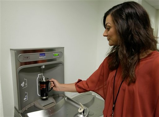 In this photo taken Thursday, July 5, 2012, Shauna Barbera uses a bottled water dispenser at the California Institute of Integral Studies in San Francisco. (AP Photo/Eric Risberg)
