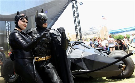 "Comic-Con attendees Katie Mitchell, left, and Jonathan Graves, from Los Angeles, strike a pose in front of the Tumbler Batmobile ""Batman Begins"" and ""The Dark Knight"" during Comic-Con, Saturday, July 14, 2012, in San Diego."