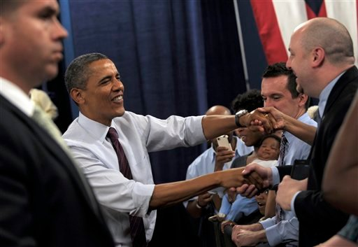 President Barack Obama greets the crowd as he arrives to speak at a campaign event at the Cincinnati Music Hall in Cincinnati, Monday, July 16, 2012. Obama is spending the day campaigning in Cincinnati. (AP Photo/Susan Walsh)