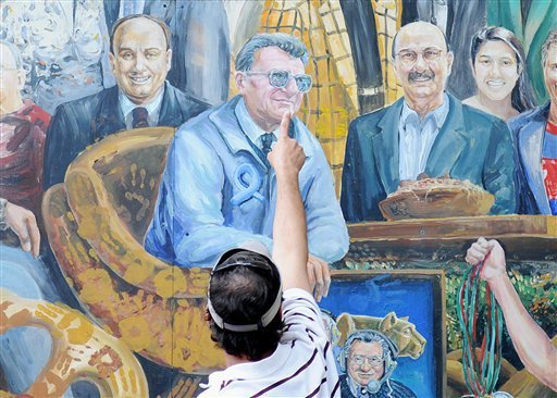 A visitor points to the spot in a mural by Michael Pilato where a halo that was above the late Penn State football coach Joe Paterno has been painted over by the artist in State College, Pa. on Saturday, July 14, 2012. (AP Photo)