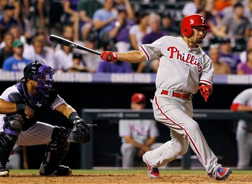 Philadelphia Phillies' Shane Victorino, right, follows the flight of his RBI triple with Colorado Rockies catcher Wilin Rosario in the ninth inning of the Phillies' 8-5 victory in a game in Denver on Saturday, July 14, 2012. (AP Photo/David Zalubowski)