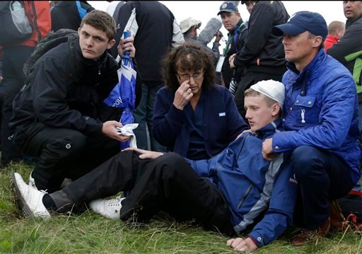 Jason Blue, age 16, from Bristol is helped by medical staff and an official after being hit by a ball from Rory McIlroy of Northern Ireland during the first round of the British Open Golf Championship, Thursday, July 19, 2012. (AP Photo/Chris Carlson)
