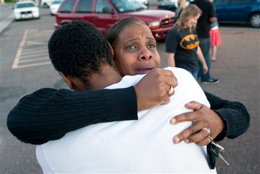 Shamecca Davis hugs her son Isaiah Bow, who was an eye witness to the shooting, outside Gateway High School where witnesses were brought for questioning Friday, July 20, 2012 in Denver.