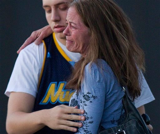 Jacob Stevens, 18, hugs his mother Tammi Stevens after being interviewed by police outside Gateway High School where witnesses were brought for questioning after a shooting at a movie theater, Friday, July 20, 2012 in Denver.