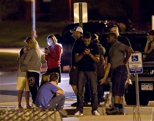 People use mobile devices as they wait outside Gateway High School where witnesses were brought for questioning after a shooting at a movie theater showing the Batman movie.