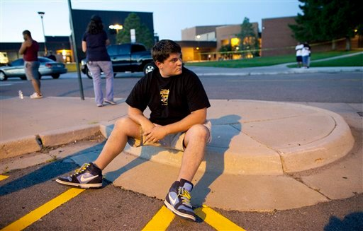 yewitness Chandler Brannon, 25, sits outside Gateway High School where witnesses were brought for questioning after a shooting at a movie theater showing the Batman movie.