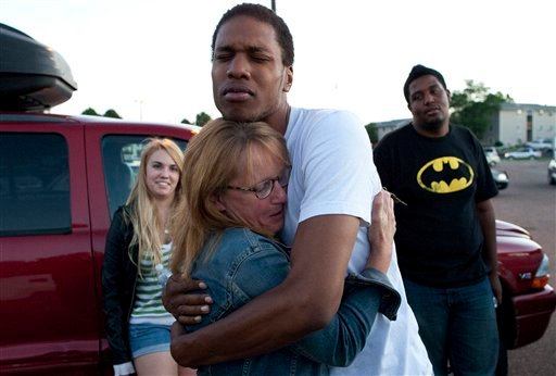 Judy Goos, center left, hugs her daughter's friend, Isaiah Bow, 20, while eyewitnesses Emma Goos, 19, left, and Terrell Wallin, 20, right, gather outside Gateway High School where witnesses were brought for questioning.