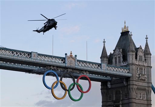 A British Royal Marine Sea King helicopter carrying the Olympic flame flies past the Tower Bridge in London, as it arrives to the Tower of London, Friday, July 20, 2012.