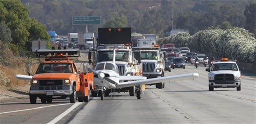 California Highway Patrol officers and Caltrans workers move a Piper single-engine plane that made an emergency landing on Interstate 15 off the freeway in Escondido, Calif.