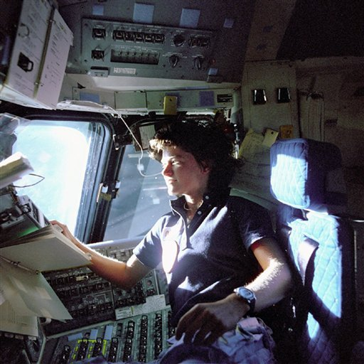 In this June 1983 photo released by NASA, astronaut Sally Ride, a specialist on shuttle mission STS-7, monitors control panels from the pilot's chair on the shuttle Columbia flight deck.