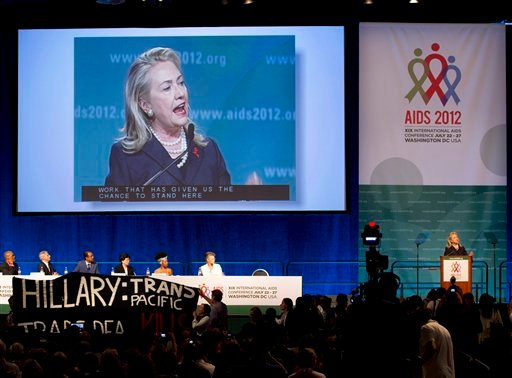 Protesters parade a banner in front of the stage as Secretary of State Hillary Rodham Clinton speaks at the XIX International Aids Conference, Monday, July 23, 2012, in Washington. (AP Photo/Carolyn Kaster)