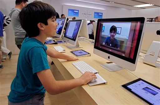 In this Thursday, July 19, 2012, photo an Apple customer Shayan Hooshmand, 11, uses PhotoBooth on a 21.5-inch iMac at an Apple store in Palo Alto, Calif. (AP Photo/Paul Sakuma)