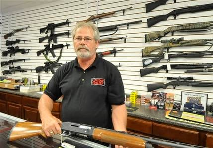 Randy Hodges holds a firearm at the Gun Vault in High Point N.C. Monday July 23, 2012. (AP Photo/The Enterprise,Sonny Hedgecock)