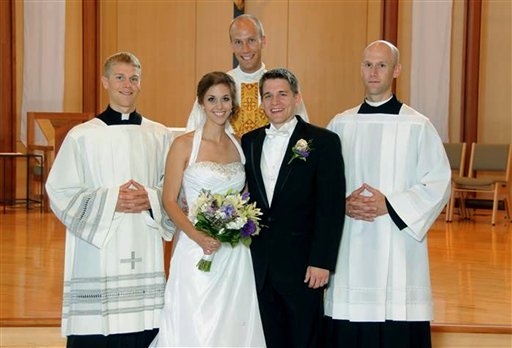 A July 23, 2011, photo provided by Bernadette Strand shows Father Luke Strand, center, after marrying sister Theresa and Christopher Krausert in Dousman, Wis. (AP Photo/Courtesy Strand Family)