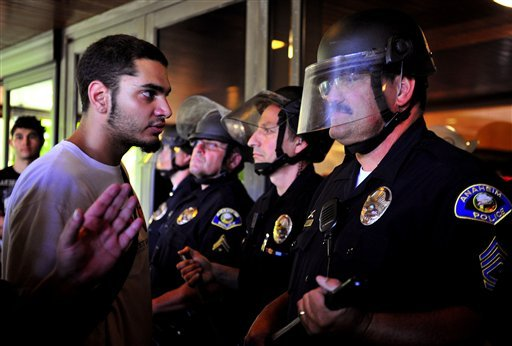 Demonstrators gather on the steps of Anaheim City Hall Tuesday, July 24, 2012, to protest the death of Manuel Diaz, 25, who died as a result of gunshot wounds sustained during a police pursuit by the Anaheim Police Department last Saturday. (AP Photo)