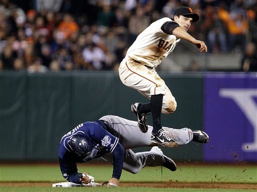 San Francisco Giants second baseman Ryan Theriot hops over San Diego Padres' Carlos Quentin after completing a double play in the sixth inning, Tuesday, July 24, 2012, in San Francisco. Padres' Yasmani Grandal was out at first base. (AP Photo/Ben Margot)