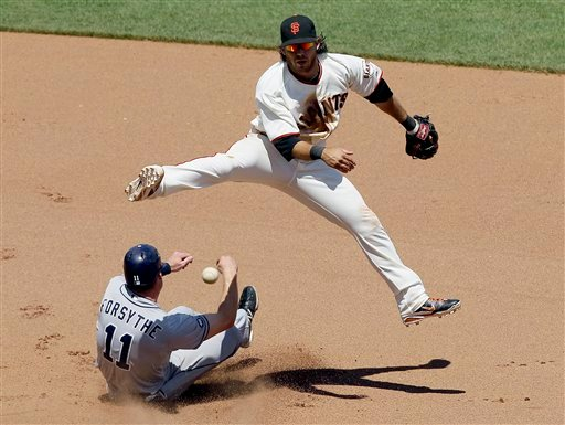 San Francisco Giants shortstop Brandon Crawford jumps over San Diego Padres' Logan Forsythe while turning a double play on a ground ball hit by Chase Headley during the seventh inning in San Francisco, Wednesday, July 25, 2012. (AP Photo/Jeff Chiu)