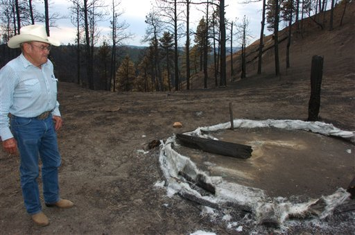A July 20, 2012 photo shows Cecil Kolka examining the remains of a fiberglass water tank in the Custer National Forest that melted during the Ash Creek Fire near Volborg, Mont. (AP Photos/Matthew Brown)