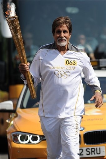 In this photo provided by LOCOG, Bollywood actor Amitabh Bachchan carries the Olympic flame on the torch relay leg between The City of London and the borough of Southwark in London, Thursday, July 25, 2012. (AP Photo/LOCOG, Yui Mok)