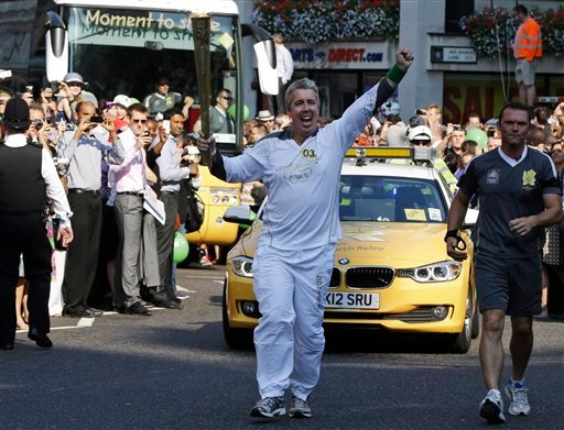 Torchbearer Kevin Crain, carries the Olympic Flame as he arrives at St. Paul's Cathedral, in central London, ahead of the 2012 Summer Olympics, Thursday, July 26, 2012. (AP Photo/Lefteris Pitarakis)