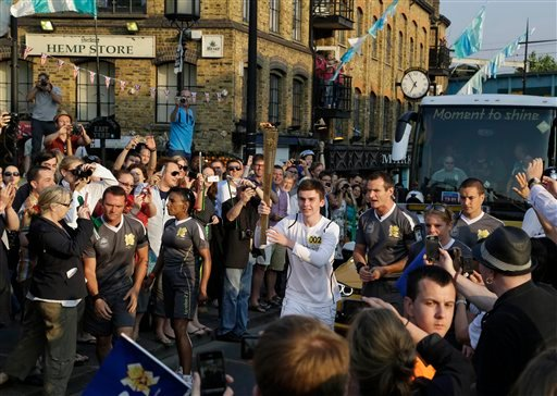 Torchbearer Darren Fitzpatrick carries the Olympic Flame through the streets of Camden in London, ahead of the 2012 Summer Olympics, Thursday, July 26, 2012. (AP Photo/Lefteris Pitarakis)