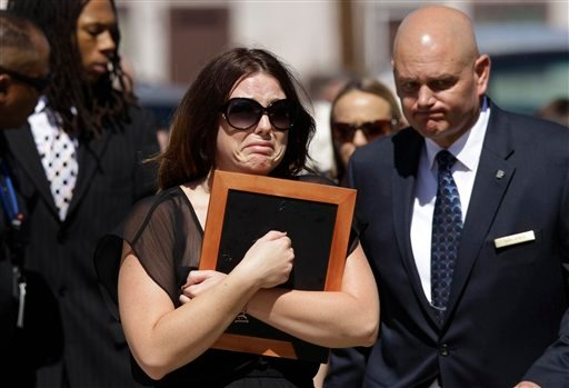Amanda Medek, sister of Micayla Medek, carrying a frame is escorted from where the family of Aurora, Colo., movie theater shooting victim Micayla Medek had gathered before Medek's funeral to the church Thursday, July 26, 2012, in Denver. (AP)