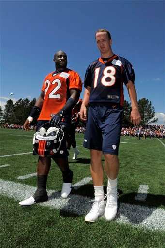 Denver Broncos quarterback Peyton Manning (18) and Elvis Dumervil (92) talks as the leave the practice field following the opening session of Denver Broncos NFL football training camp in Englewood, Colo., Thursday, July 26, 2012.