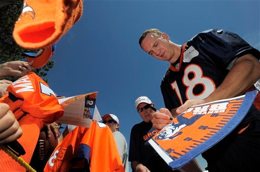 Denver Broncos quarterback Peyton Manning signs autographs for fans following the opening session of Denver Broncos NFL football training camp.