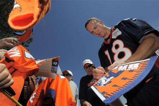 Denver Broncos quarterback Peyton Manning signs autographs for fans following the opening session of Denver Broncos NFL football training camp.