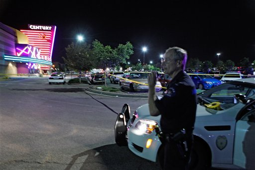 In this July 20, 2012 file photo, an Aurora Police officer talks on his radio outside the Century 16 movie theatre in Aurora, Colo., at the scene of a mass shooting.