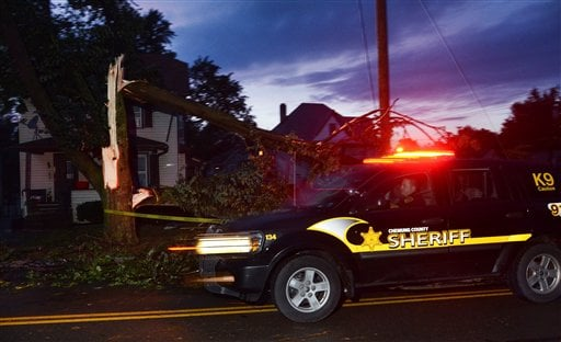 A Chemung County Sheriff rushes past a felled tree after a possible tornado struck the area, Thursday, July 26, 2012, in Elmira N.Y.