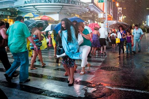 A pedestrian rushes through a torrential downpour in Times Square, Thursday, July 26, 2012, in New York.