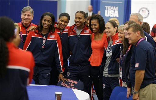 First lady Michelle Obama poses for a photo with members of the women's basketball team after speaking at a breakfast with Team USA at the 2012 Summer Olympics, Friday, July 27, 2012, in London.