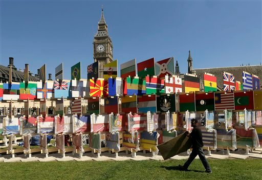 A worker carries a board while installing a display of international flags across the street from Big Ben Tuesday, July 24, 2012, in London.