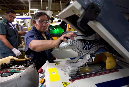 FILE - In this Tuesday, May 1, 2012, file photo, worker Maria Contrero, of Boston, removes an elite running shoe from a sole press during the assembly process at the New Balance Athletic Shoe, Inc. factory in Boston. (AP Photo/Steven Senne, File)