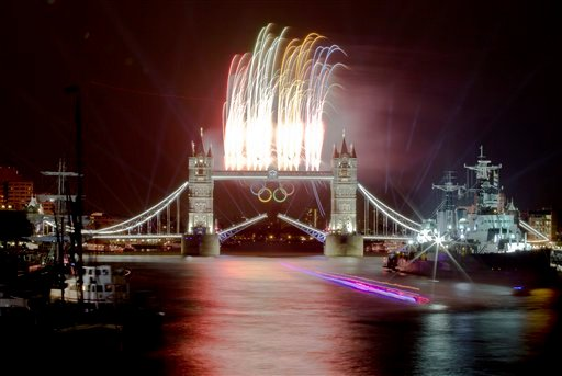 A speedboat carrying the Olympic Flame leaves a trail on this slow exposure photograph as fireworks explode above the iconic Tower Bridge over the River Thames in central London. (AP Photo/Vadim Ghirda)