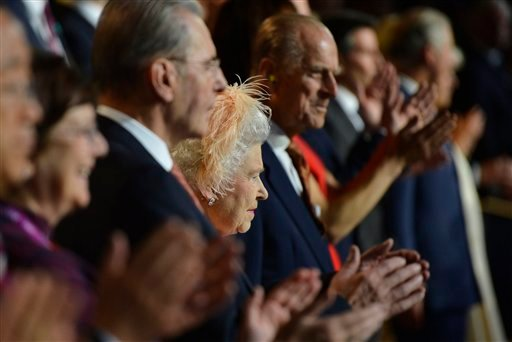 Britain's Queen Elizabeth II, center, is flanked by Britain's Prince Philip, the Duke of Edinburgh, and IOC President Jacques Rogge, left, as she attends the Opening Ceremony of the 2012 Olympic Summer Games at the Olympic Stadium in London. (AP)