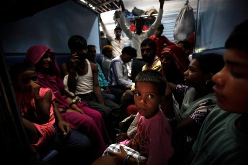 Passengers sit in a train and wait for power to get restored at a railway station in New Delhi, India, Monday, July 30, 2012. (AP Photo/Rajesh Kumar Singh)