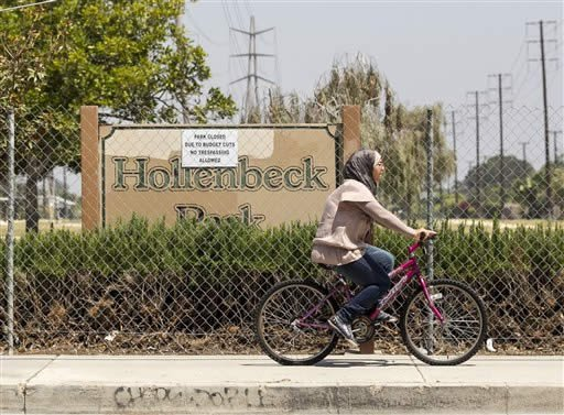 """In this photo taken Friday, July 27, 2012, a cyclist rides past the closed Hollenbeck Park in Stanton, Calif. A sign posted on the chain-link fence reads """"park closed due to budget cuts - no trespassing allowed."""" (AP Photo/Damian Dovarganes)"""