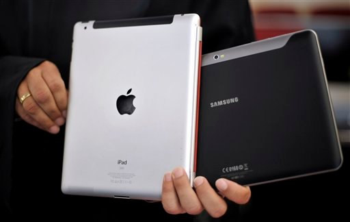 FILE - In this Aug. 25, 2011 file photo, an attorney holds an Apple iPad, left, and a Samsung Galaxy Tab 10.1 at the regional court in Duesseldorf, Germany. (AP Photo/dapd, Sascha Schuermann, File)