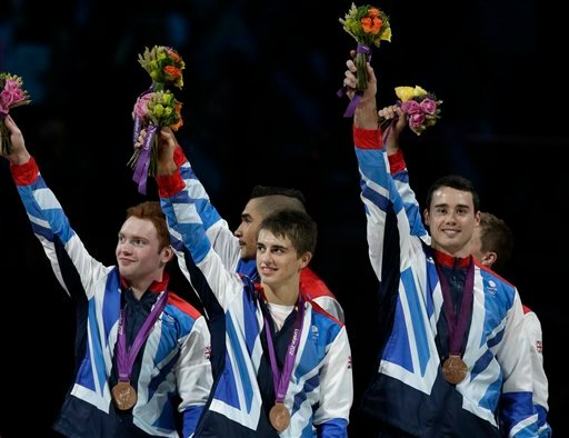 Great Britain's gymnasts Daniel Purvis, left, Max Whitlock, center, Louis Smith, back left, Kristian Thomas, front right, and Sam Oldham, partly hidden back right, waves from the podium during the medal ceremony of the Artistic Gymnastic men's team final.