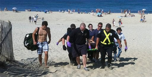 In this Monday, July 30, 2012 photo, Christopher Myers is carried off Ballston Beach in Truro, Mass., after sustaining bite wounds to his legs while swimming. (AP Photo/Cape Cod Times, Eric Williams)