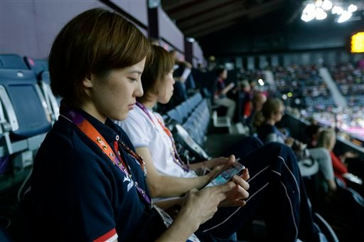 Japan's Miyuki Maeda looks at her iphone as she watches badminton matches in progress with a phone in her hand at the 2012 Summer Olympics, Tuesday, July 31, 2012, in London. (AP Photo/Saurabh Das)