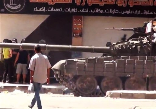 This image made from amateur video released by Shaam News Network and accessed Tuesday, July 31, 2012, purports to show a man walking past Syrian a military tank in Damascus, Syria. (AP Photo/Shaam News Network via AP video)