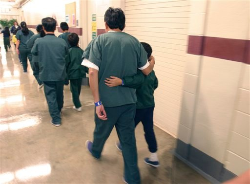 A Feb. 9, 2007 file photo provided by the Department of Homeland Security shows family detainees walking down the hall at the T. Don Hutto Residential Center in Taylor, Texas. (AP Photo/Department of Homeland Security, Charles Reed, HO, File)