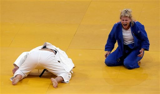 Kayla Harrison of the United States reacts while competing against Mayra Aguiar of Brazil, (in white),